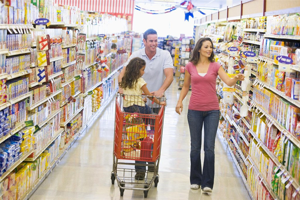 A family of 3 walking down an aisle in a grocery store