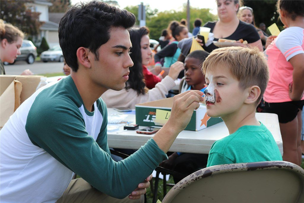 A boy having his face painted like an animal
