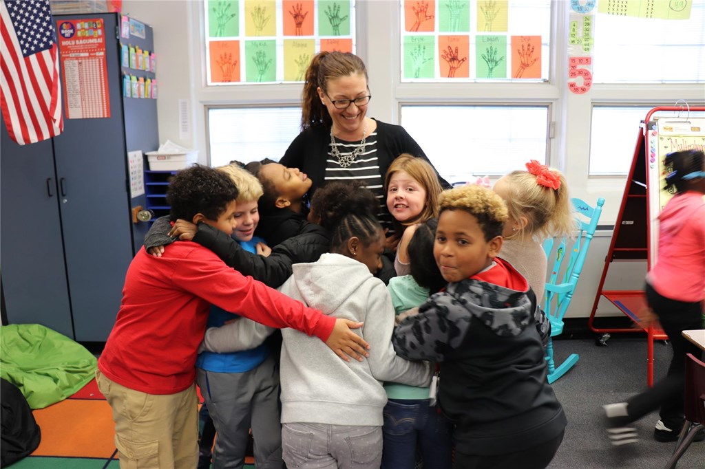 Teacher with students hugging her