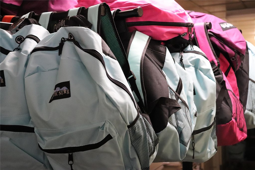 Backpacks hang on a rack