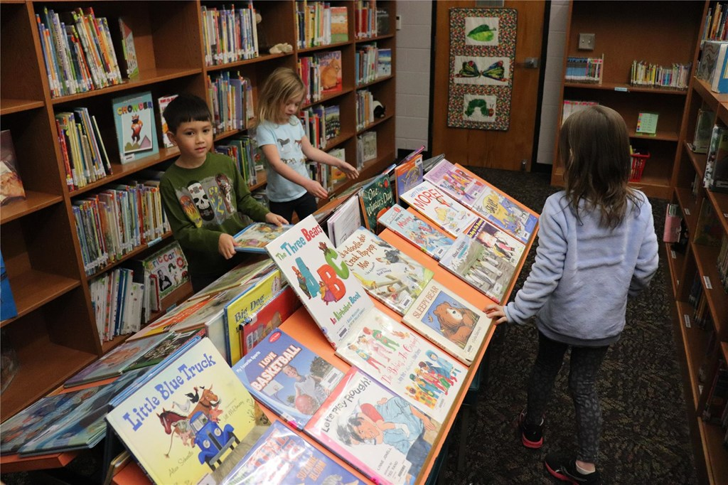 3 children looking at books in a library