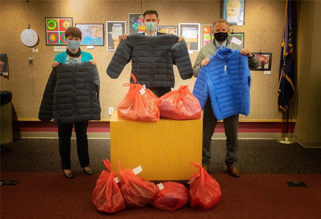 District administrators hold up donated coats.