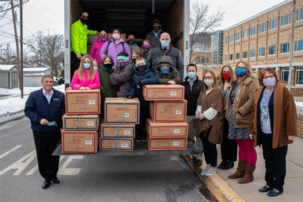 Students pose as truck delivers coats.