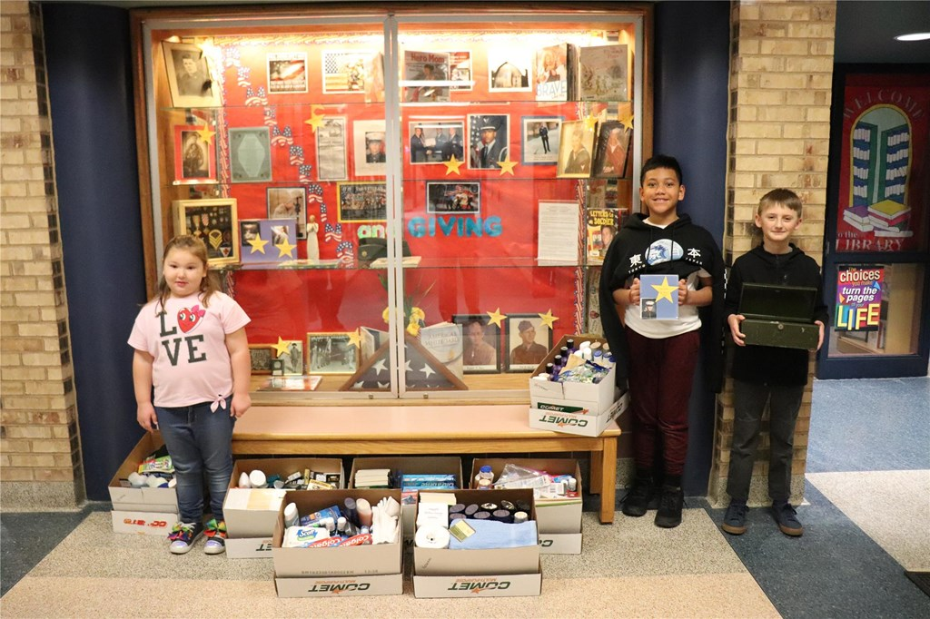 Students stand with donated items.