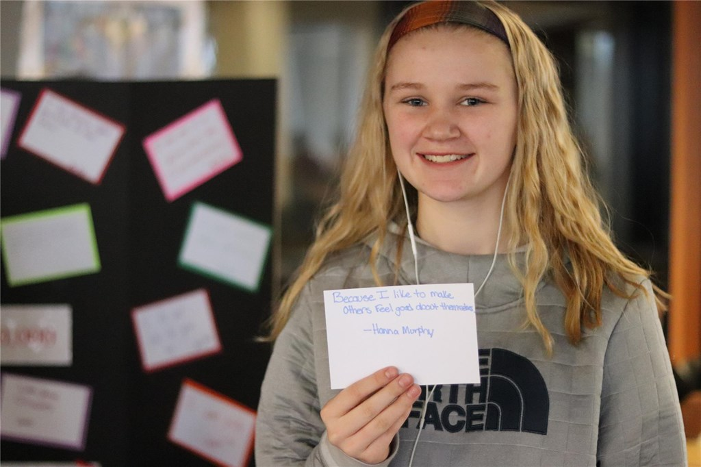 Student displays her one in a million card.