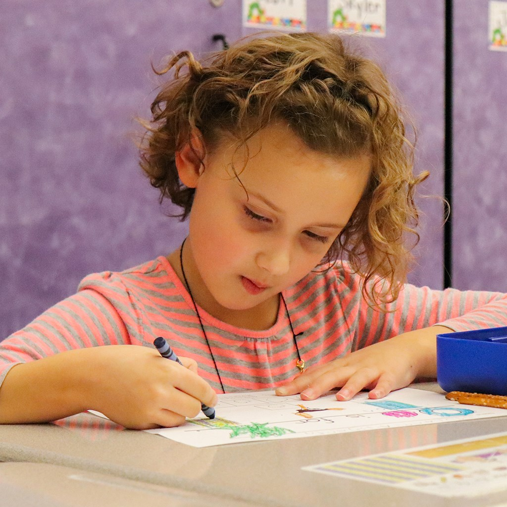 Young girl coloring with crayon